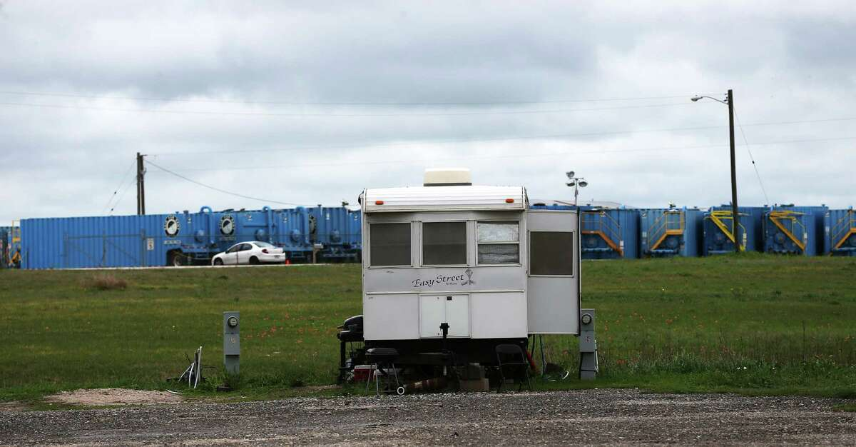 Idled frac tanks are seen in a lot behind an RV parked in the Pecan Grove RV Resort in Kenedy, Texas, Thursday, March 10, 2016. Once thriving in activity from drilling in the Eagle Ford Shale, Karnes and other counties in the play are seeing the effects of the slow down in drilling due to an oil glut. In late 2014 the Organizations of Petroleum Exporting Countries increased production. This led to an oil glut, a drop in the price oil and drilling activity in the U.S. shale areas. The Texas rig count has dropped by 625 rigs since the start of 2015, to 227 now.