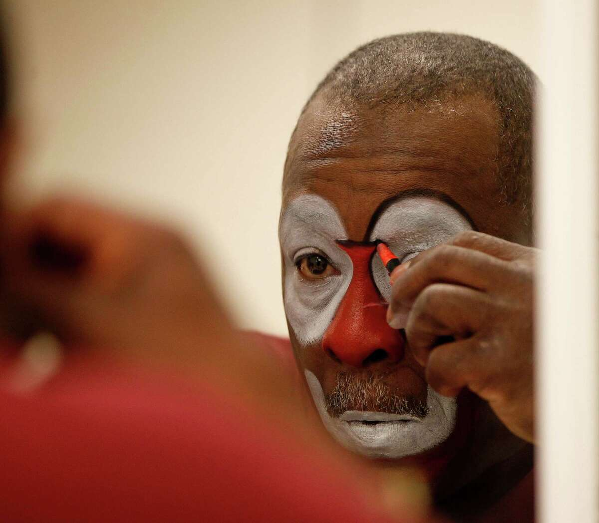 Famed rodeo barrelman, Leon Coffee, puts on his makeup before the start of the Houston Livestock Show and Rodeo at NRG Stadium, Friday, March 11, 2016.