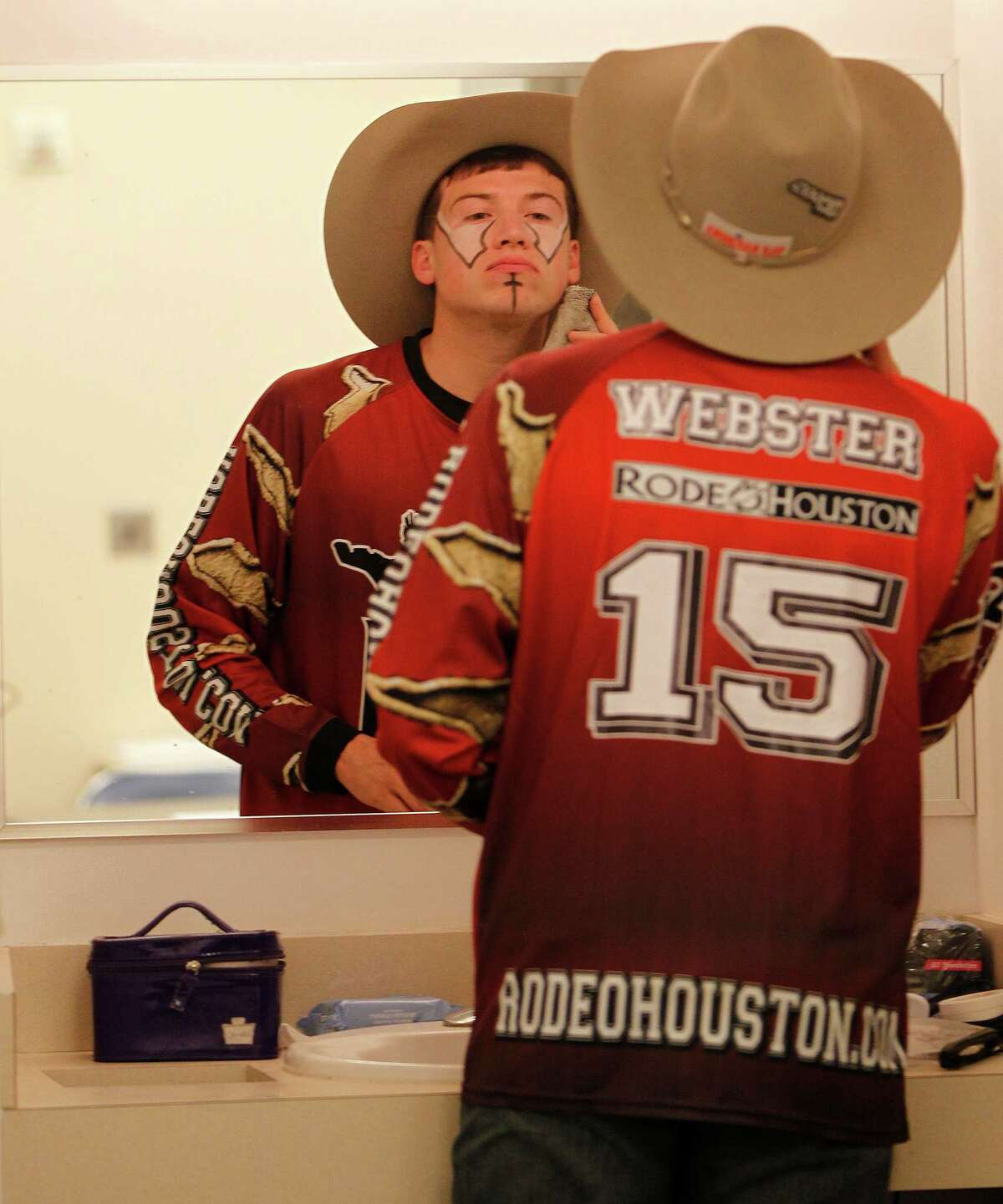 Bullfighter Cody Webster puts on his makeup before the start of the Houston Livestock Show and Rodeo at NRG Stadium, Friday, March 11, 2016.