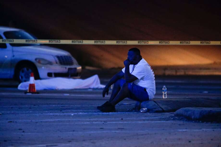 A man sits at the scene of a fatal officer-involved shooting at the intersection of  Collingsworth Street and the Eastex Freeway, Saturday, March 12, in Houston. ( Jon Shapley / Houston Chronicle ) Photo: Jon Shapley, Chronicle