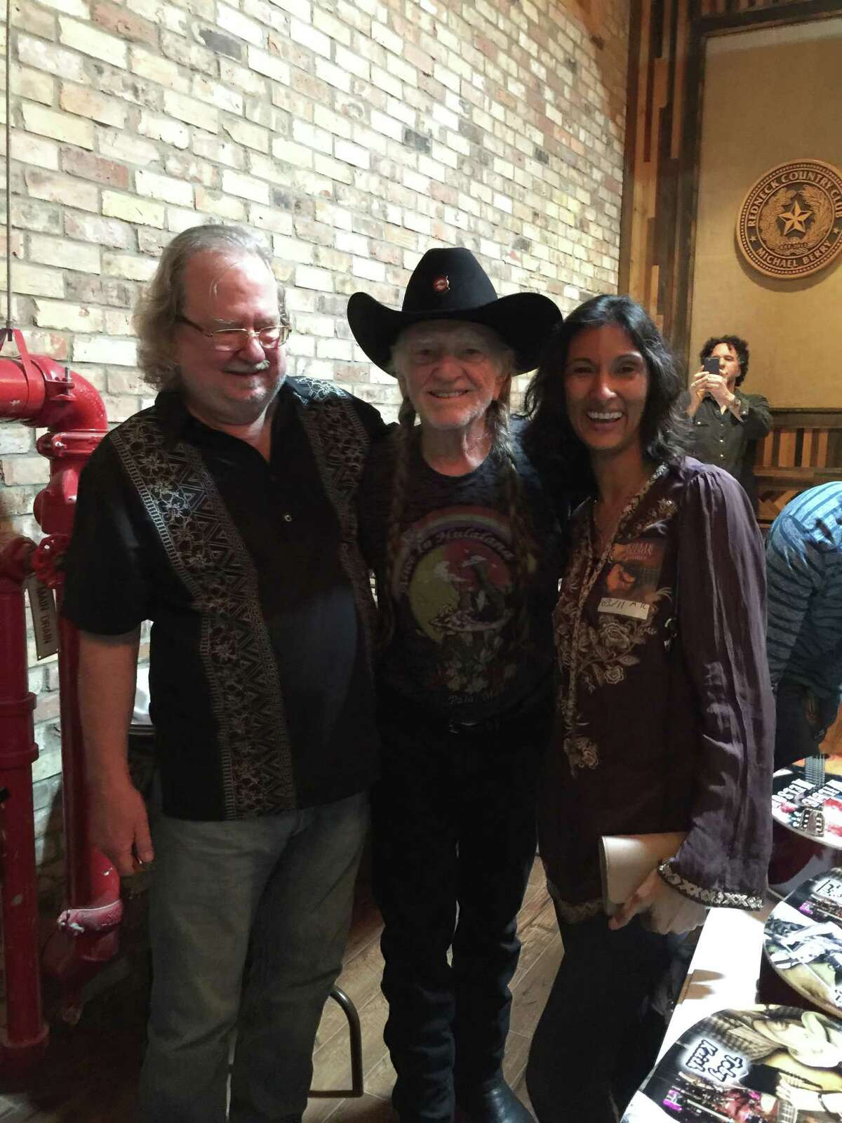 """Immunologist James Allison and wife, Dr. Padmanee Sharma, with singer Willie Nelson after Allison joined him on stage to play harmonica for one of the """"top five moments"""" of his life."""