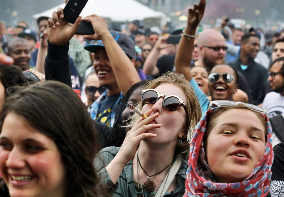 With the Colorado state capitol building visible in the background, partygoers dance to live music and smoke pot on the first of two days at the annual 4/20 marijuana festival in Denver, Saturday April 19, 2014. The annual event is the first 420 marijuana celebration since retail marijuana stores began selling in January 2014. (AP Photo/Brennan Linsley) ORG XMIT: COBL109 Photo: Brennan Linsley / AP