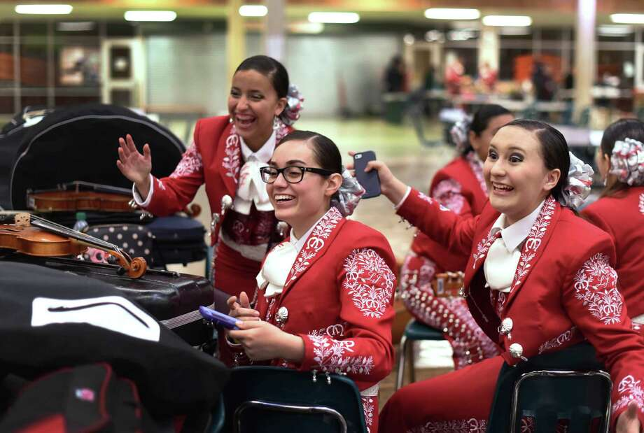 Getzemany Garcia (second from left) and Victoria Garcia (right) of La Joya High School wait for their mariachi group to perform during the first-ever University Interscho lastic League State Mariachi Festival, held at Southwest High School. Photo: Billy Calzada /San Antonio Express-News / San Antonio Express-News