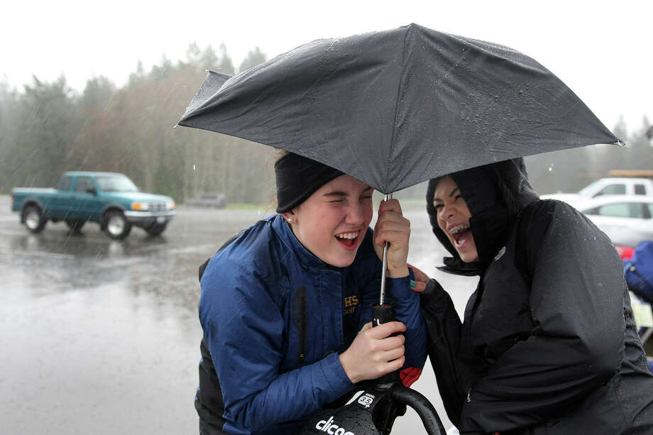 Bremerton High School golfers Lily Gelhaus, center, and Alyssa Ronquillo huddle underneath a small umbrella as the wind and heavy rain beat down on them at Gold Mountain Golf Course on Thursday, March 10, 2016. They were there to play in a match against North Mason, but it was canceled because the greens had standing water on them. Photo: Larry Steagall, AP / Kitsap Sun
