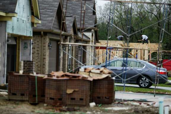 Builders work on a new home in the Springfield Estates development Thursday, March 10, 2016 in Baytown. ( Michael Ciaglo / Houston Chronicle )
