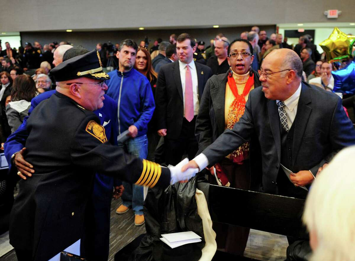 Armando Perez, acting Chief of Police for Bridgeport Police Department, at left, shakes hands with Wilbur Chapman before taking the oath of office at a Swearing-in Ceremony at City Hall Common Council Chambers in Bridgeport, Conn., on Thursday Mar. 3, 2016.