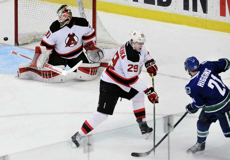 Utica Comets' #21 Chris Higgins, right, has his shot stopped by Albany Devils' #29 Raman Hrabarenka and goalie Scott Wedgewood, left, during Saturday's game at the Times Union Center March 12, 2016 in Albany, NY.  (John Carl D'Annibale / Times Union) Photo: John Carl D'Annibale / 10035791A