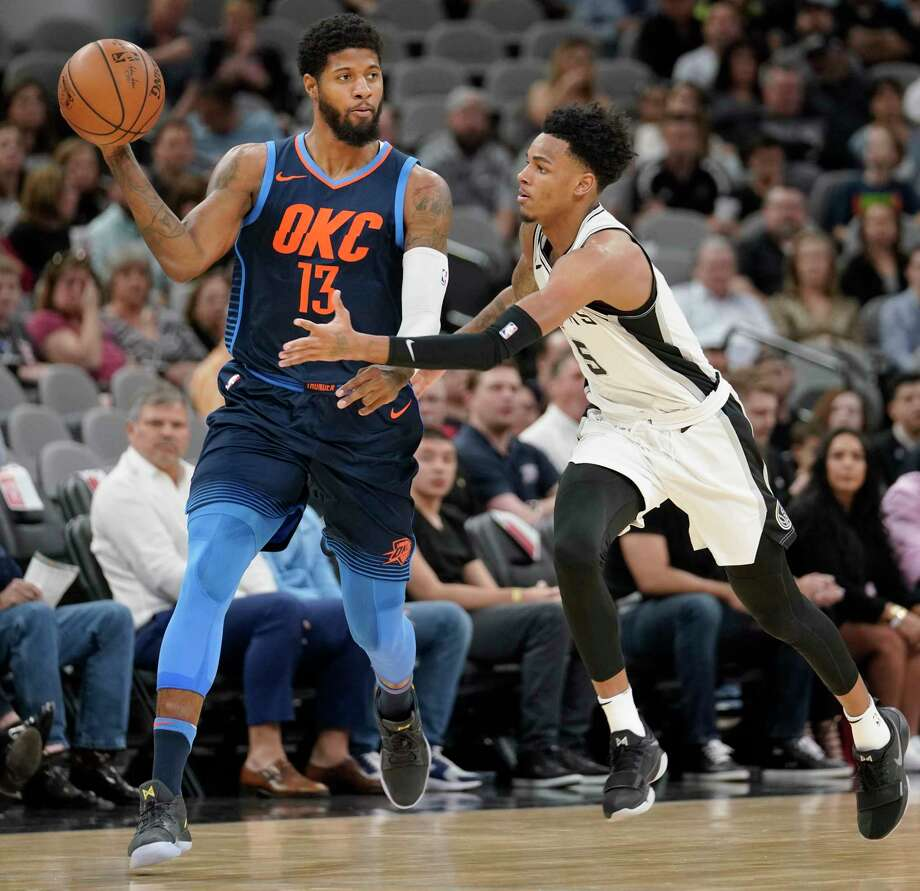 Oklahoma City Thunder's Paul George (13) looks to pass around San Antonio Spurs' Dejounte Murray during the first half of an NBA basketball game Thursday, March 29, 2018, in San Antonio. (AP Photo/Darren Abate) Photo: Darren Abate, Associated Press / FR115 AP