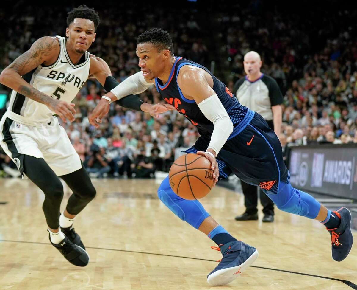 Oklahoma City Thunder's Russell Westbrook, right, drives against San Antonio Spurs' Dejounte Murray during the first half of an NBA basketball game Thursday, March 29, 2018, in San Antonio. (AP Photo/Darren Abate)