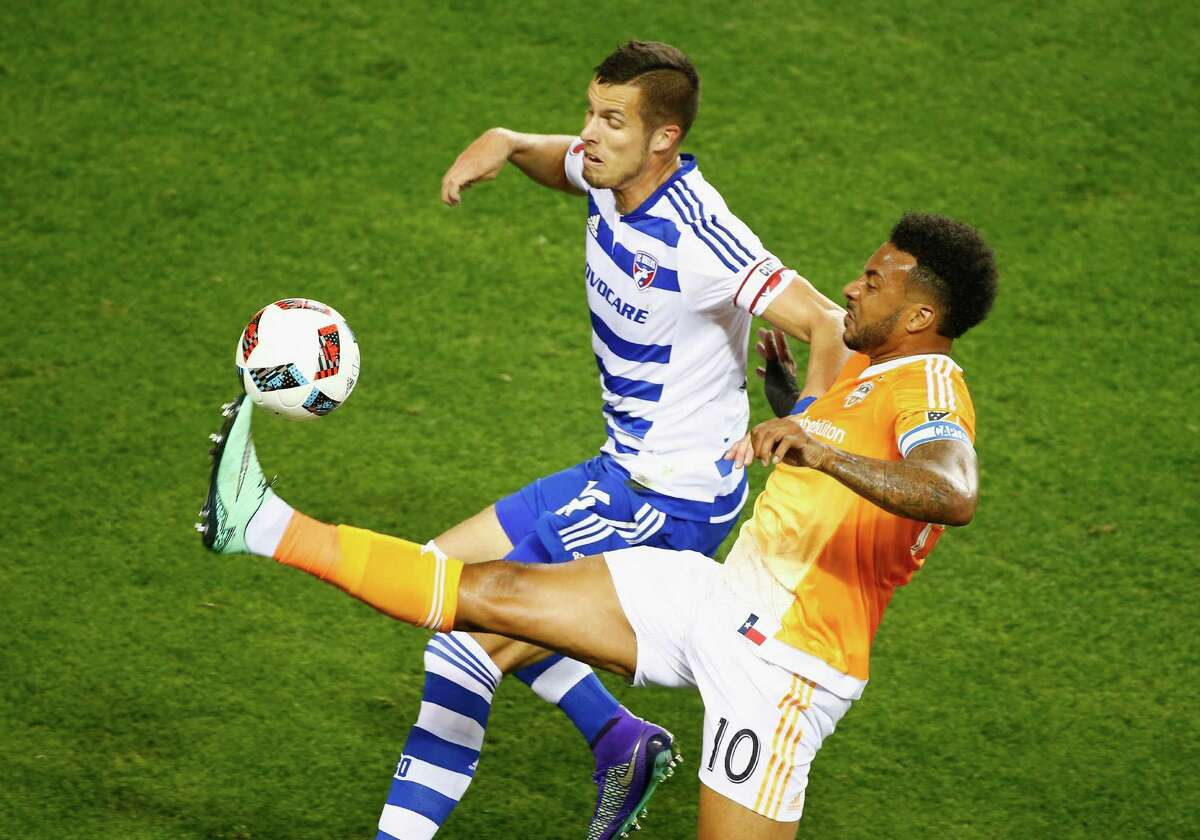 HOUSTON, TX - MARCH 12: Giles Barnes #10 of the Houston Dynamo battles for the ball with Matt Hedges #24 of FC Dallas during their game at BBVA Compass Stadium on March 12, 2016 in Houston, Texas.
