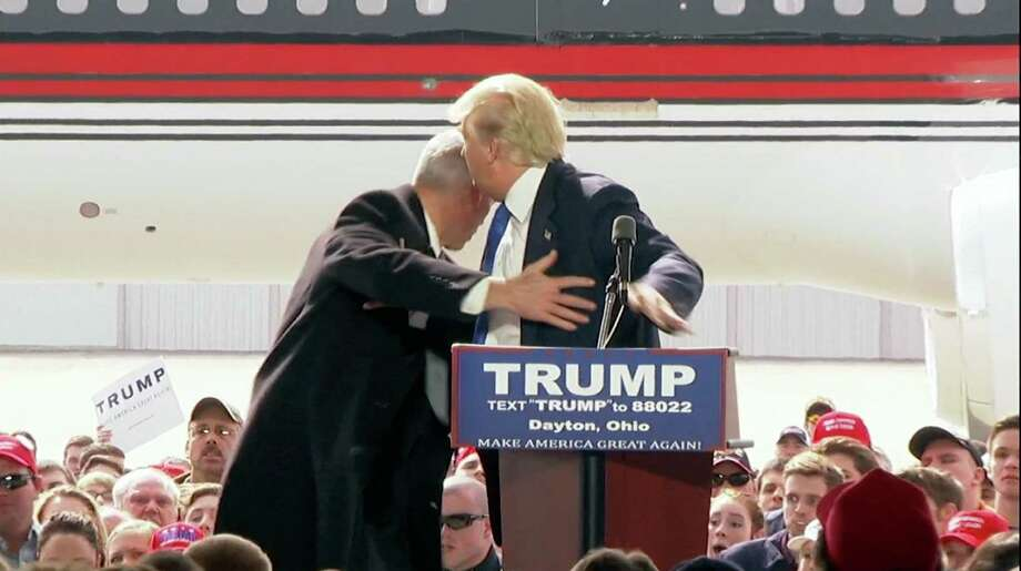 In this image from the TV network pool, a U.S. Secret Service agent rushes onto stage to form a protective ring around Republican presidential candidate Donald Trump after someone tried to rush the stage as he spoke at a campaign rally at Wright Brothers Aero Hangar for a rally, Saturday, March 12, 2016, in Vandalia, Ohio. (TV Network Pool via AP)  ORG XMIT: OHJE101 / TV Network Pool