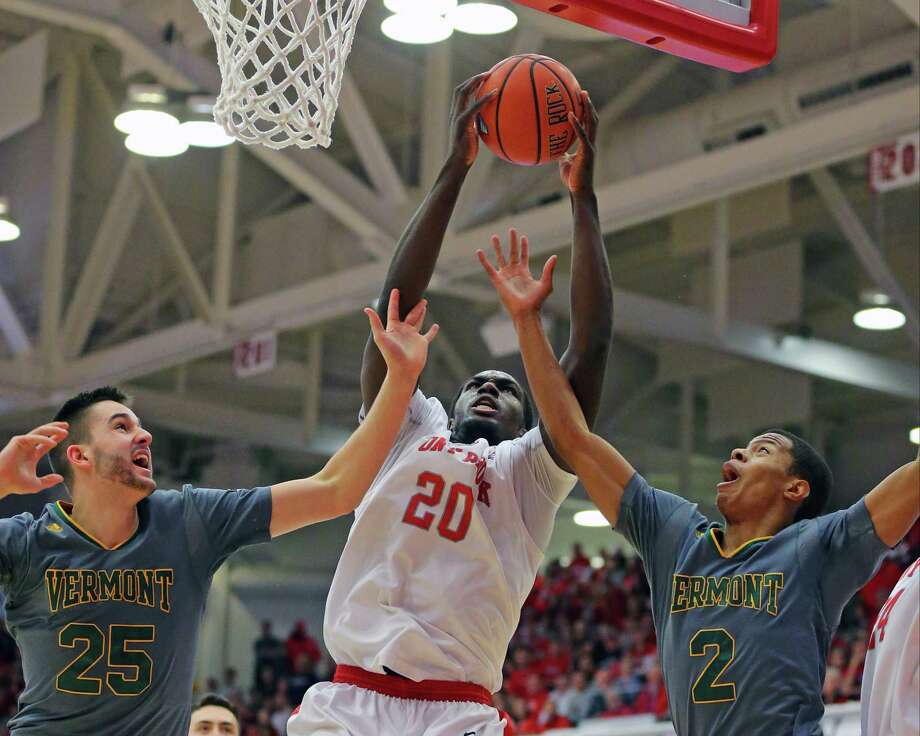 Stony Brook's Jameel Warney, center, grabs an offensive rebound over Vermont's Drew Urquhart, left, and Trae Bell-Haynes during the first half of an NCAA college basketball game in the championship of the  American East Conference men's tournament, Saturday, March 12, 2016, in Stony Brook, N.Y. (Daniel De Mato/Newsday via AP) NYC OUT, NO SALES ORG XMIT: NYANE503 Photo: Daniel De Mato / Daniel De Mato Photography Inc. 2016