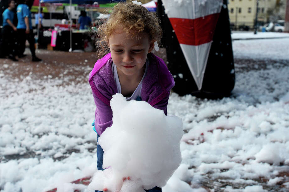 Jayla Coffey, 6, plays in the artificial snow on Crockett Street during the 3rd Annual Snow Run & Walk 5k in downtown Beaumont on Saturday morning. Photo taken Saturday 3/12/16 Ryan Pelham/The Enterprise Photo: Ryan Pelham / ©2016 The Beaumont Enterprise/Ryan Pelham