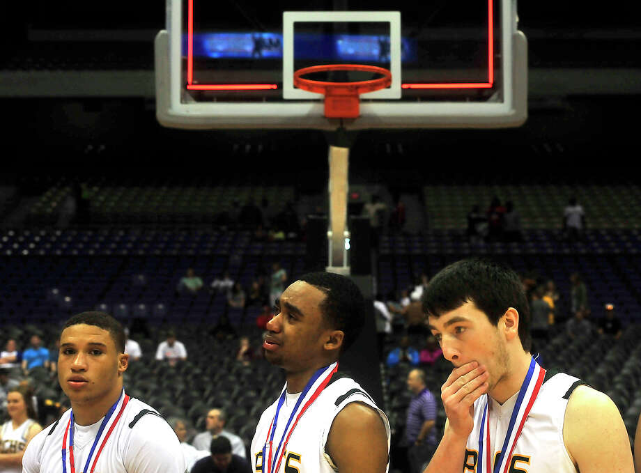 East Chambers' Stevie Johnson is emotional as the Buccaneers, including Antwann Anderson (left) and Graham Devillier, line up and receive their runner-up medals after falling to Brownfield during Saturday's Class 3A state final championship game at the Alamodome. Photo taken Saturday, March 12, 2016 Kim Brent/The Enterprise Photo: Kim Brent / Beaumont Enterprise