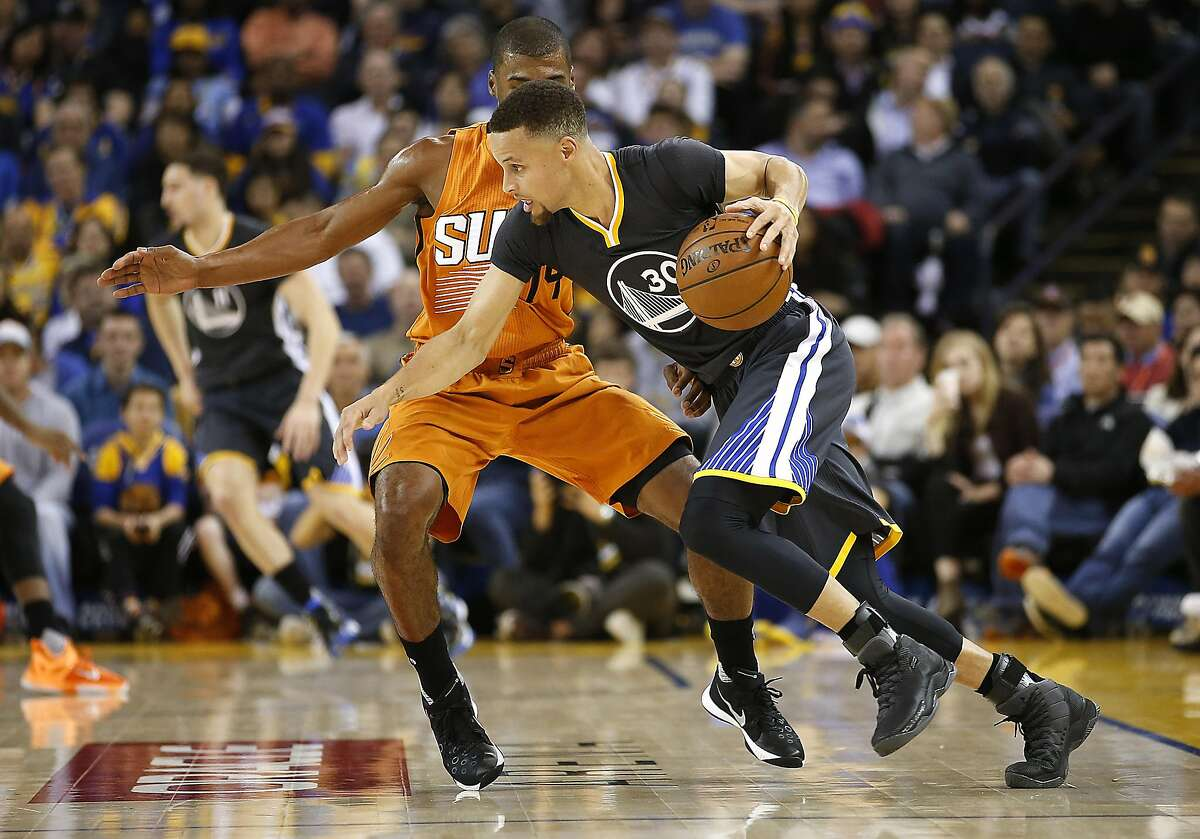 Golden State Warriors' Stephen Curry, right, drives the ball against Phoenix Suns guard Ronnie Price (14) during the first half NBA game at Oracle Arena in Oakland, Calif., on Saturday, March 12, 2016.