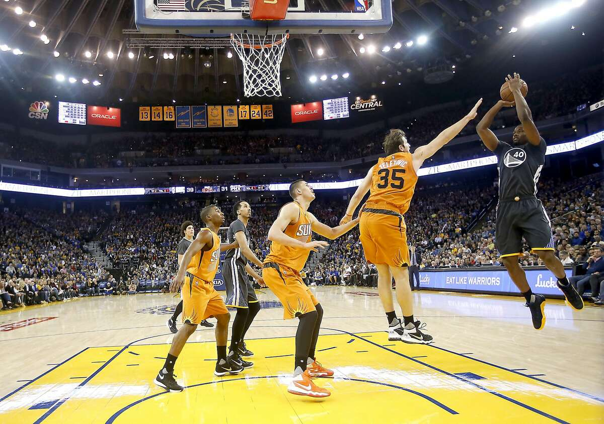 Golden State Warriors forward Harrison Barnes, right, puts up a shot over Phoenix Suns forward Mirza Teletovic (35) during the first half NBA game at Oracle Arena in Oakland, Calif., on Saturday, March 12, 2016.