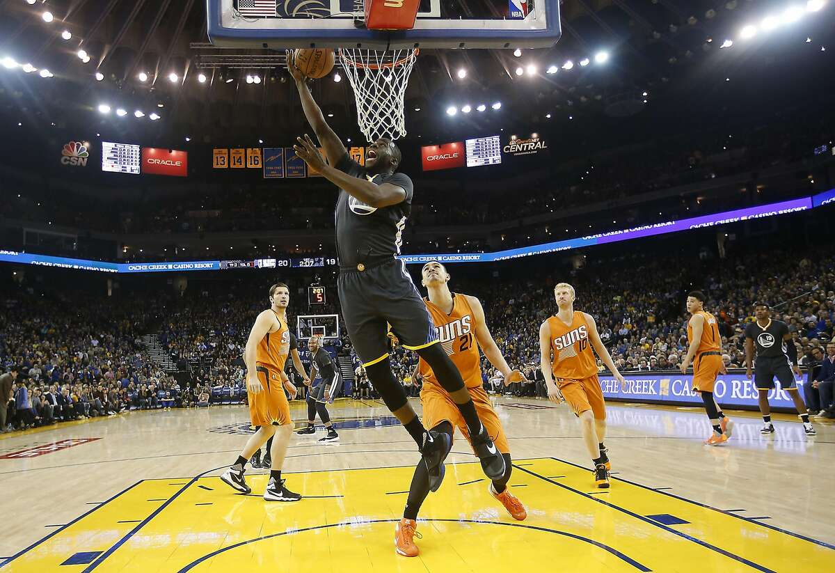 Golden State Warriors forward Draymond Green (23) drives to the basket against Phoenix Suns center Alex Len (21) during the first half NBA game at Oracle Arena in Oakland, Calif., on Saturday, March 12, 2016.