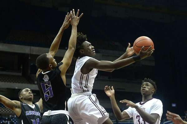 Silsbee's Devon McCain looks to connect with the basket as Dallas Lincoln's Kortrijk Miles defends during Saturday's Class 4A state final championship game at the Alamodome. Photo taken Saturday, March 12, 2016 Kim Brent/The Enterprise