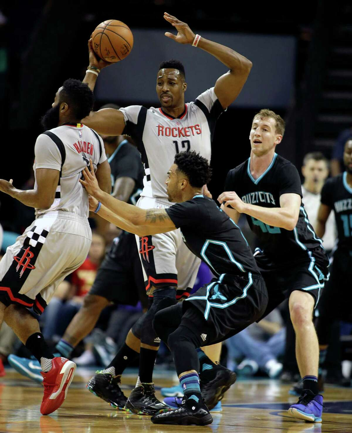 Houston Rockets' Dwight Howard, center, looks confused as he looks to pass the ball to an open teammate as he is guarded by Charlotte Hornets' Cody Zeller, right, during the first half of an NBA basketball game in Charlotte, N.C., Saturday, March 12, 2016. Houston Rockets' James Harden, left, tries to find some spacing as he his pushed in the back by Charlotte Hornets' Courtney Lee, middle. The Hornets won 125-109.
