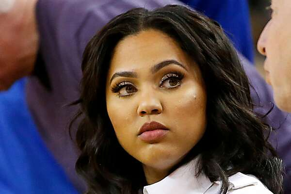 Ayesha Curry, left, wife of Golden State Warriors Stephen Curry, talks with Golden State Warriors owner Joseph Lacob, right, on the sidelines during the NBA game against Phoenix Suns at Oracle Arena in Oakland, Calif., on Saturday, March 12, 2016.