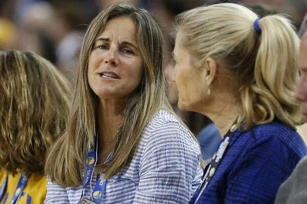 Former soccer player Brandi Chastain, left, looks on from the sidle seats as the Golden State Warriors played Phoenix Suns during the second half NBA game at Oracle Arena in Oakland, Calif., on Saturday, March 12, 2016.