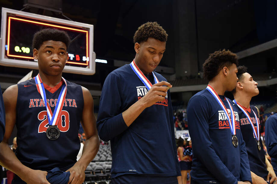 Atascocita junior forward Fabian White, center, with senior forward Mekhi Cannon (20), checks out his silver medal after the Eagles 73-54 loss to Desoto in their Class 6A boys basketball state championship game at the Alamodome in San Antonio on Saturday, Mar. 12, 2016. (Photo by Jerry Baker/Freelance) Photo: Jerry Baker, For The Houston Chronicle