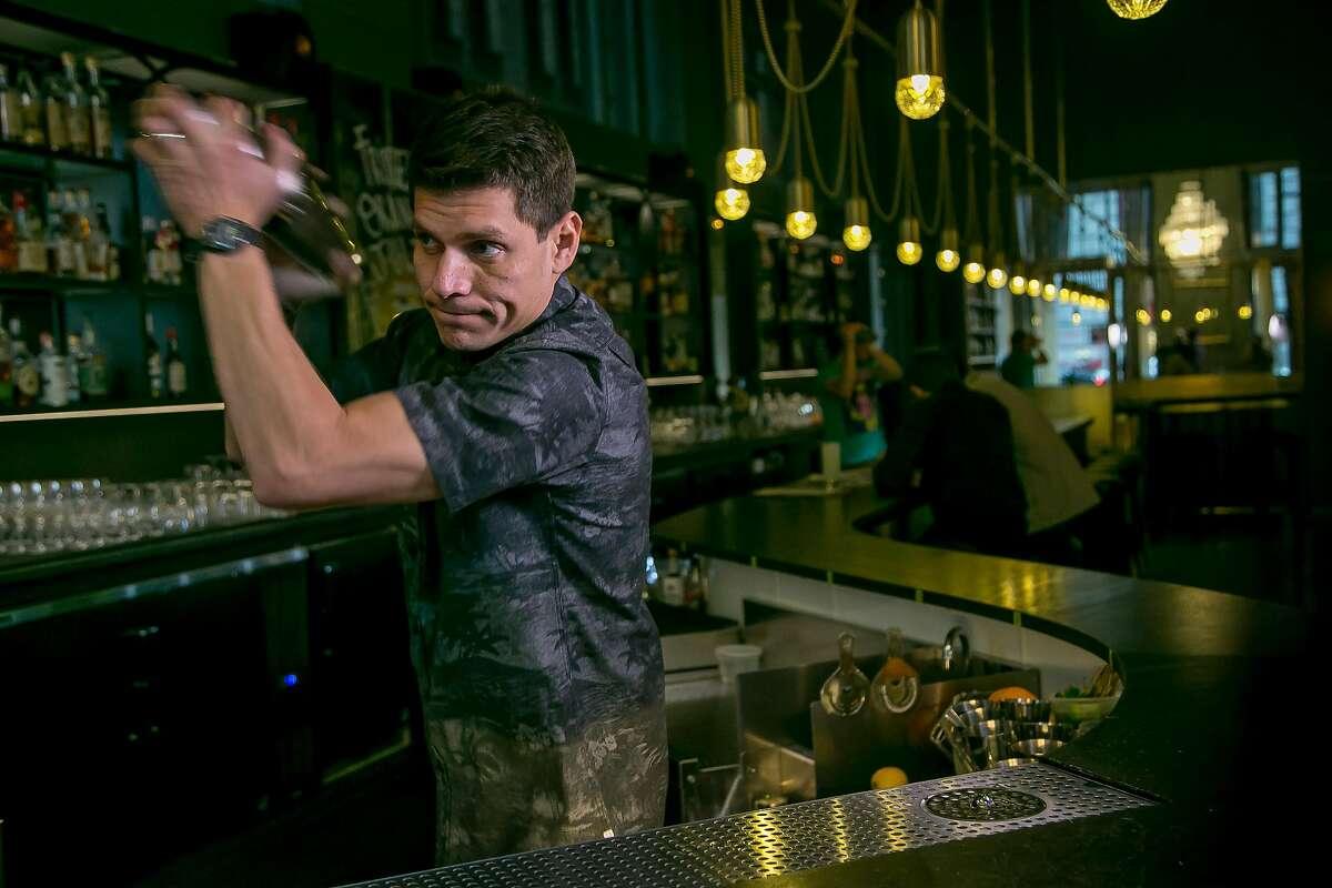Bartender Carlos Yturria shakes the