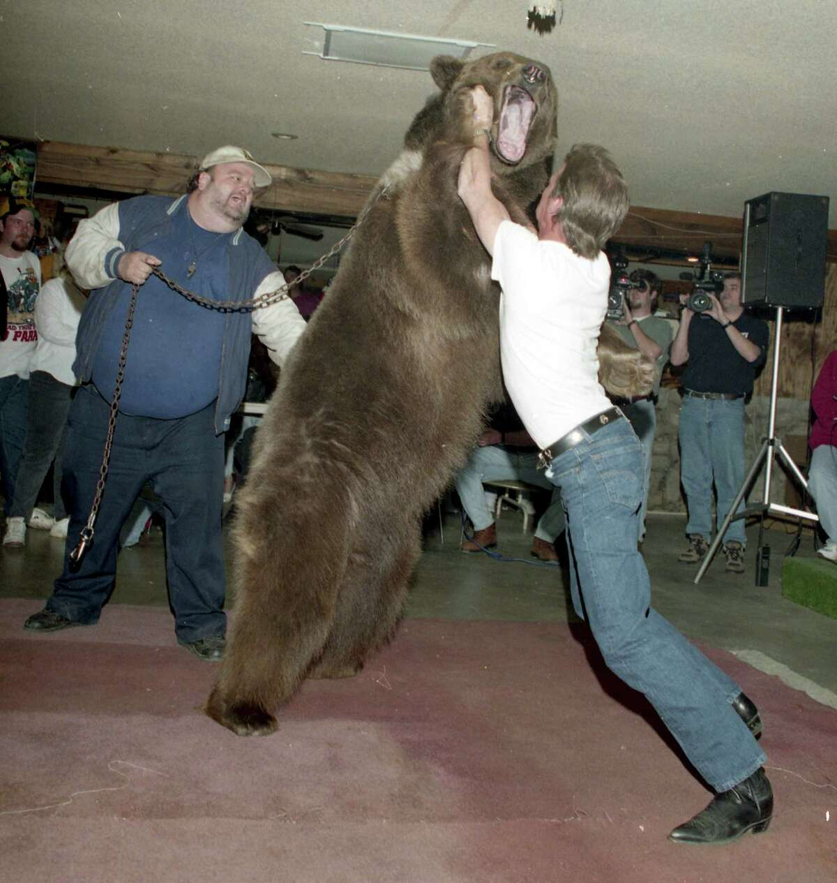 TIL: In this 1996 photo, a man wrestles a bear named Terrible Ted at the Ponderosa Club in New Hope, Ala. Bear wrestling was, for many years, considered by many to be an entertaining test of one's brute strength. Others, however, criticized it as animal cruelty. (William McCormick/AL.com via AP)