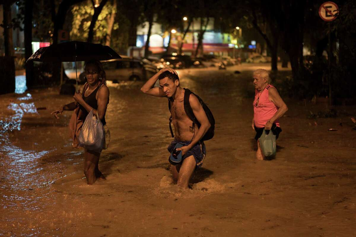 People wade through a flooded street at the Gavea neighborhood after heavy rains in Rio de Janeiro, Brazil, Saturday, March 12, 2016. Authorities in Rio declared state of crisis after torrential rains flooded parts of the city late Saturday leaving cars, buses and residents stranded.