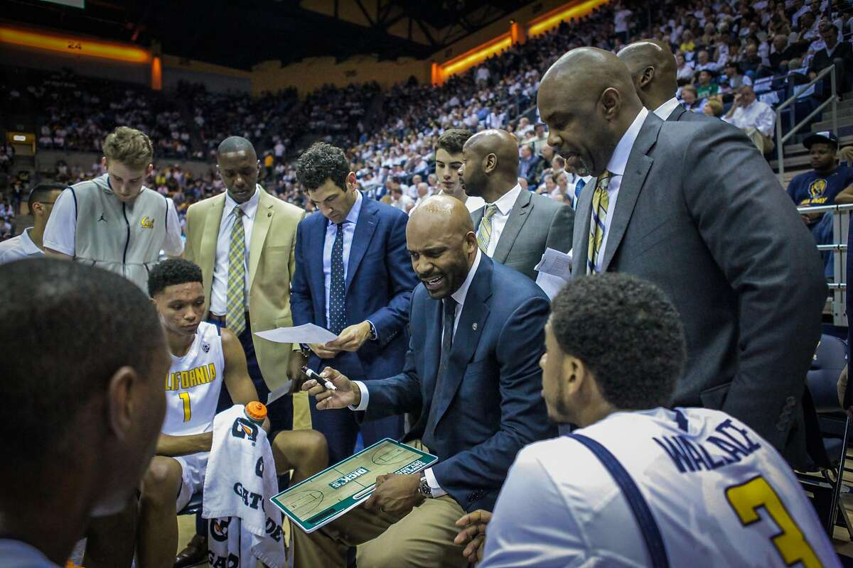 Cal assistant coach Yann Hufnagel (blue suit) stands to the left of head coach Cuonzo Martin during a Feb. 25 game against UCLA.