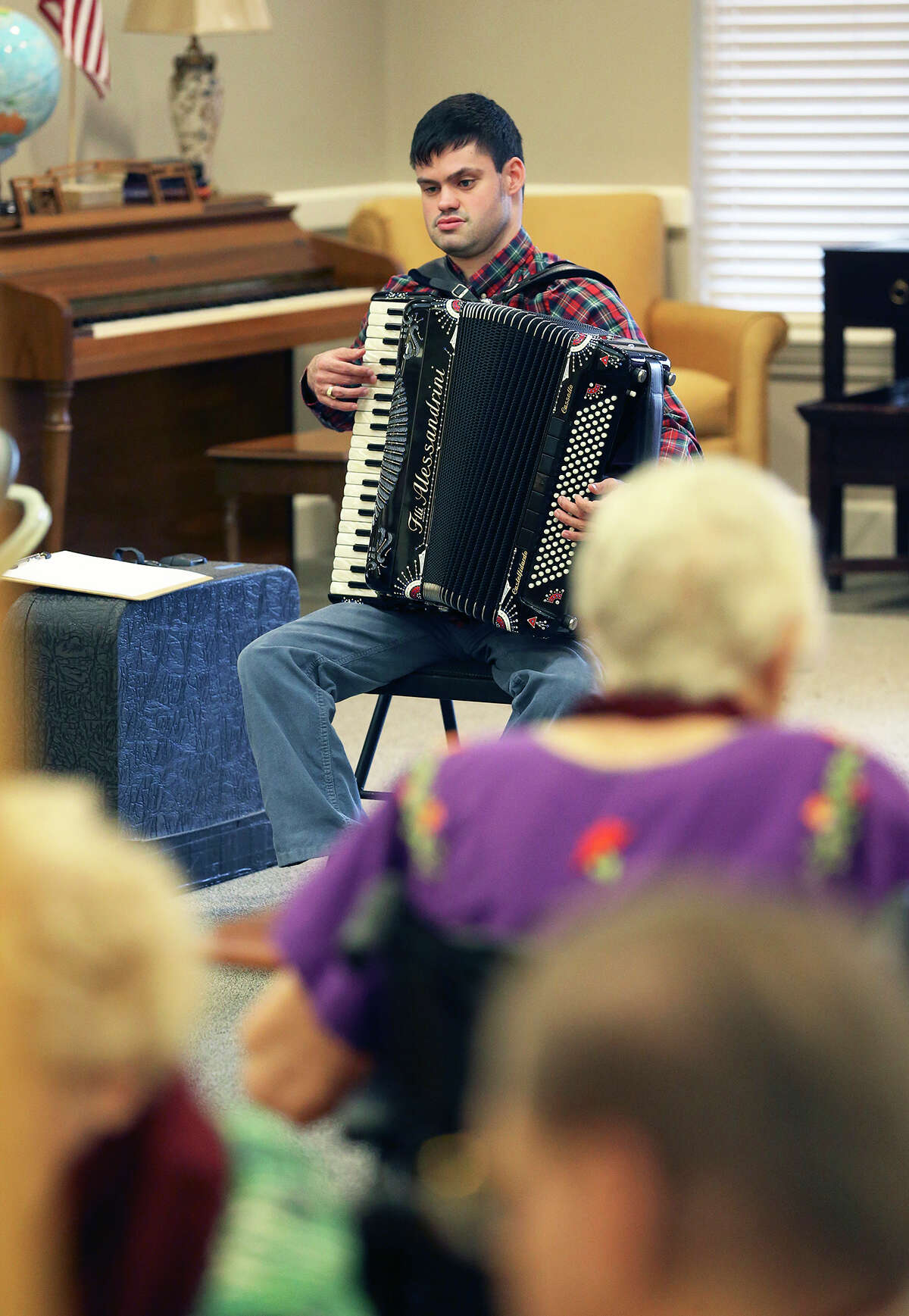John McDonald, who has the developmental disorder Asperger's syndrome, which affects his ability to socialize and communicate effectively, performs a song on the accordion at the Kendall House Retirement Home in Boerne on Wednesday. McDonald is a good example of what autism experts advise all parents of autistic kids to do: Identify and cultivate their child's special interests and talents as early as possible to improve the odds they'll be able to make their own way in the world.