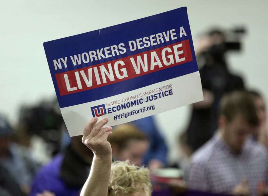 A person holds a sign during a rally to raise the minimum wage on Thursday, Feb. 25, 2016, in Albany, N.Y. New York Gov. Andrew Cuomo is continuing his push to raise the minimum wage to $15. (AP Photo/Mike Groll) ORG XMIT: NYMG109 ORG XMIT: MER2016022516103263 Photo: Mike Groll / Copyright 2016 The Associated Press. All rights reserved. This m