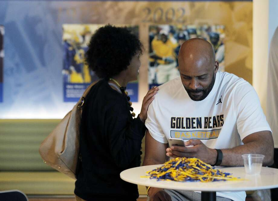 Head coach Cuonzo Martin gets a pat on the shoulder from his wife, Roberta Martin as he checks his phone after the Cal men's basketball team watched the NCAA men's basketball tournament selection show in Memorial Stadium in Berkeley, Calif., on Sunday, March 13, 2016. The Bears earned a No. 4 seed to play against Hawaii in Spokane. Photo: Carlos Avila Gonzalez, The Chronicle