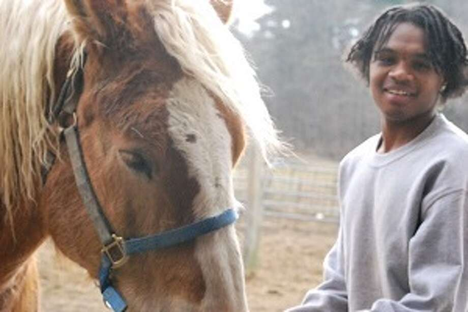 Duane W.,a student with the Berkshire Farms Workforce Development Program, learns work ethics and responsibility through caring for the animals on campus.
