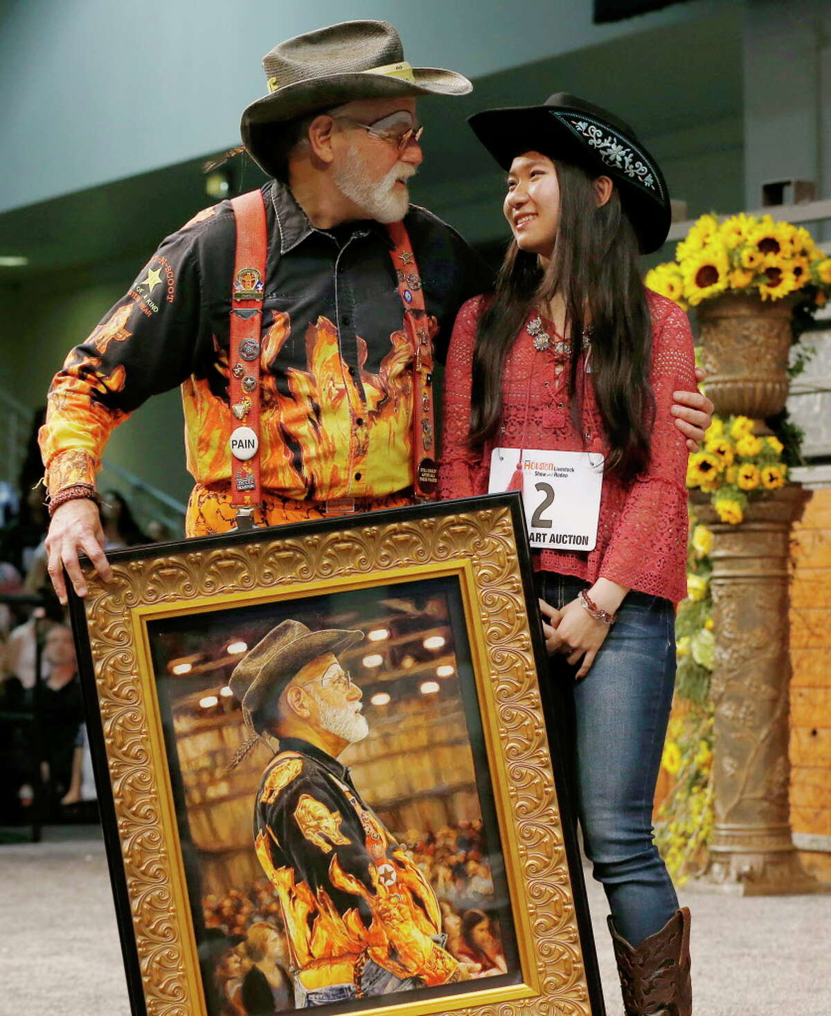 Richard Gruen hugs Lucy Chen, the 2016 Reserve Grand Champion, as he holds her painting,