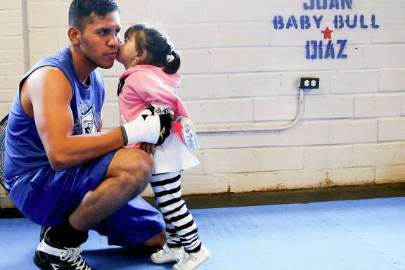 Lightweight boxer Juan Diaz gets a kiss from his daughter, Kimberly, during his workout  on Thursday, March 10, 2016, in Houston.
