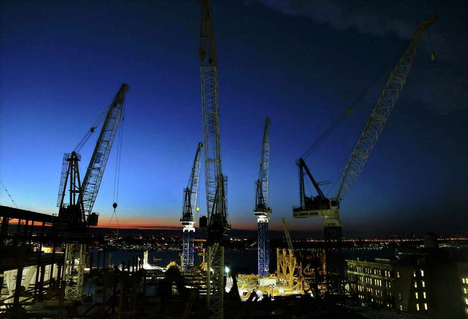 In this March 4, 2016 photo, cranes move loads of materials at dusk at the Hudson Yards construction site in New York. The steel behemoths are sprouting up all over the city, a prime force in New York's building boom capped by a sea of skyscrapers that are changing the famed urban skyline. (AP Photo/Julie Jacobson) ORG XMIT: NYJJ201 Photo: Julie Jacobson / Copyright 2016 The Associated Press. All rights reserved. This m