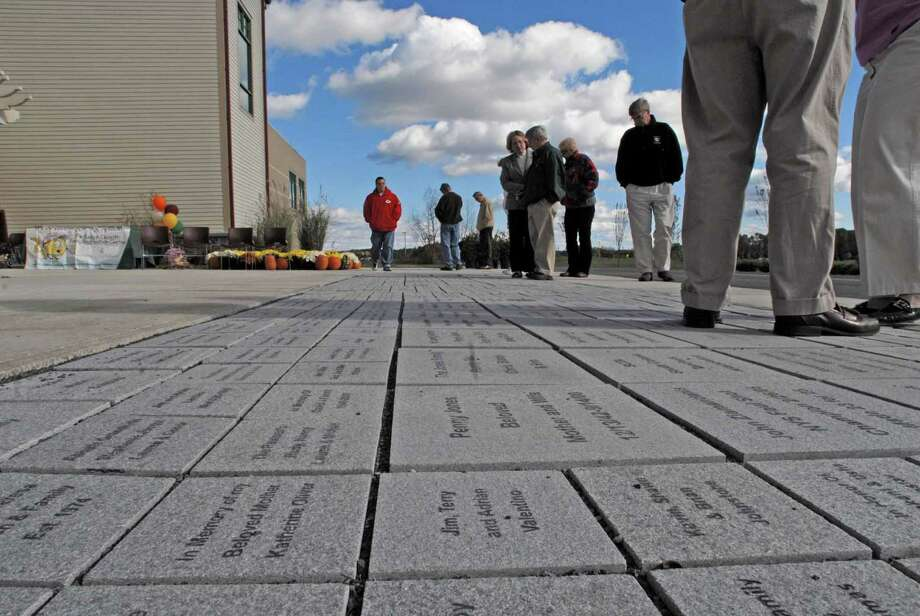 Times Union staff photo by Paul Buckowski ---     Visitors look over the pavers engraved with names  at the Rudy A. Ciccotti Family Recreation Center in Colonie, NY on Sunday, Oct. 28, 2007.  The pavers were sold during the campaign to raise money for the building of the center which opened this past past January.  Over 500 pavers were sold. The Colonie Youth Center hosted the reception to unveil the pavers. Photo: Paul Buckowski / Albany Times Union