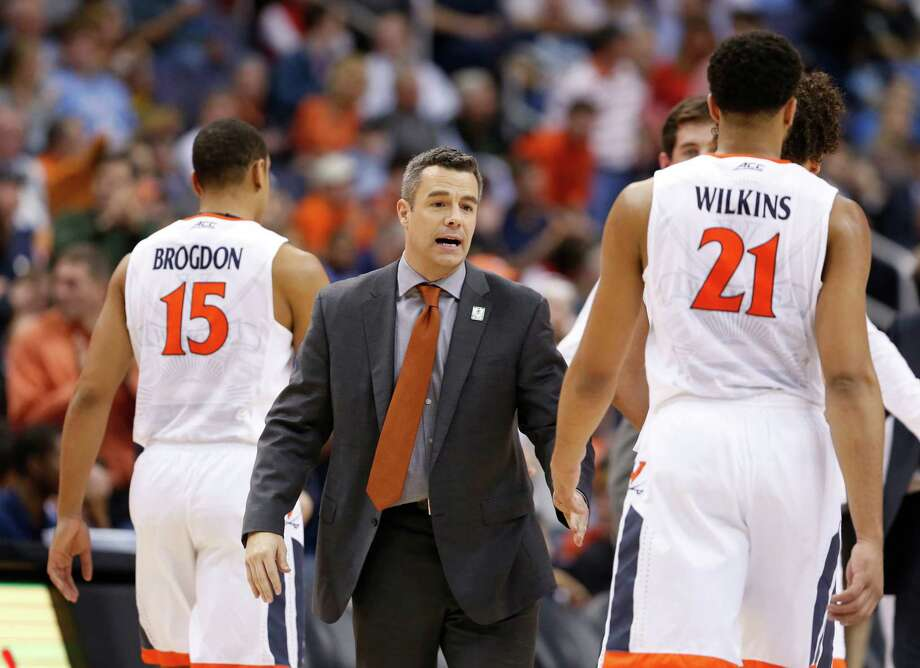 Virginia coach Tony Bennett welcomes guard Malcolm Brogdon (15) and forward Isaiah Wilkins (21) back to the bench during the second half of an NCAA college basketball game against Georgia Tech in the Atlantic Coast Conference men's tournament in Washington on Thursday, March 10, 2016. Virginia defeated Georgia Tech 72-52. (AP Photo/Steve Helber) ORG XMIT: VZN236 Photo: Steve Helber / Copyright 2016 The Associated Press. All rights reserved. This m