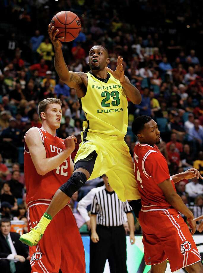 Oregon forward Elgin Cook shoots over Utah forward Jakob Poeltl, left, and Utah forward Dakarai Tucker during the second half of an NCAA college basketball game in the championship of the Pac-12 men's tournament Saturday, March 12, 2016, in Las Vegas. Oregon won 88-57. (AP Photo/John Locher) ORG XMIT: NVJL130 Photo: John Locher / Copyright 2016 The Associated Press. All rights reserved. This m