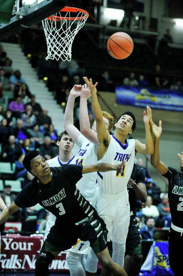 Darius Celestin, left, of Elmont Memorial and Troy's Jack McLaren, center, and Brandon Holmes battle for a rebound during their New York State Class A basketball final on Sunday, March 13, 2016, in Glens Falls, N.Y.  (Paul Buckowski / Times Union) Photo: PAUL BUCKOWSKI / 10035777A