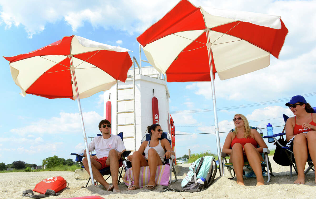 Lifeguards try to stay cool under beach umbrellas while on duty at Gulf Beach in Milford, Conn. on Tuesday July 16, 2013.