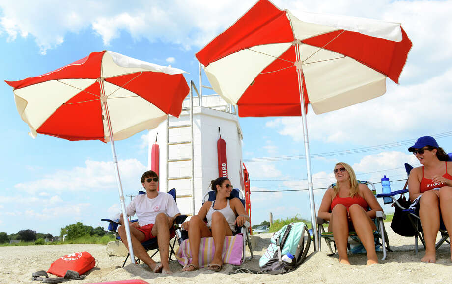 Lifeguards try to stay cool under beach umbrellas while on duty at Gulf Beach in Milford, Conn. on Tuesday July 16, 2013.  Photo: Christian Abraham / Christian Abraham / Connecticut Post