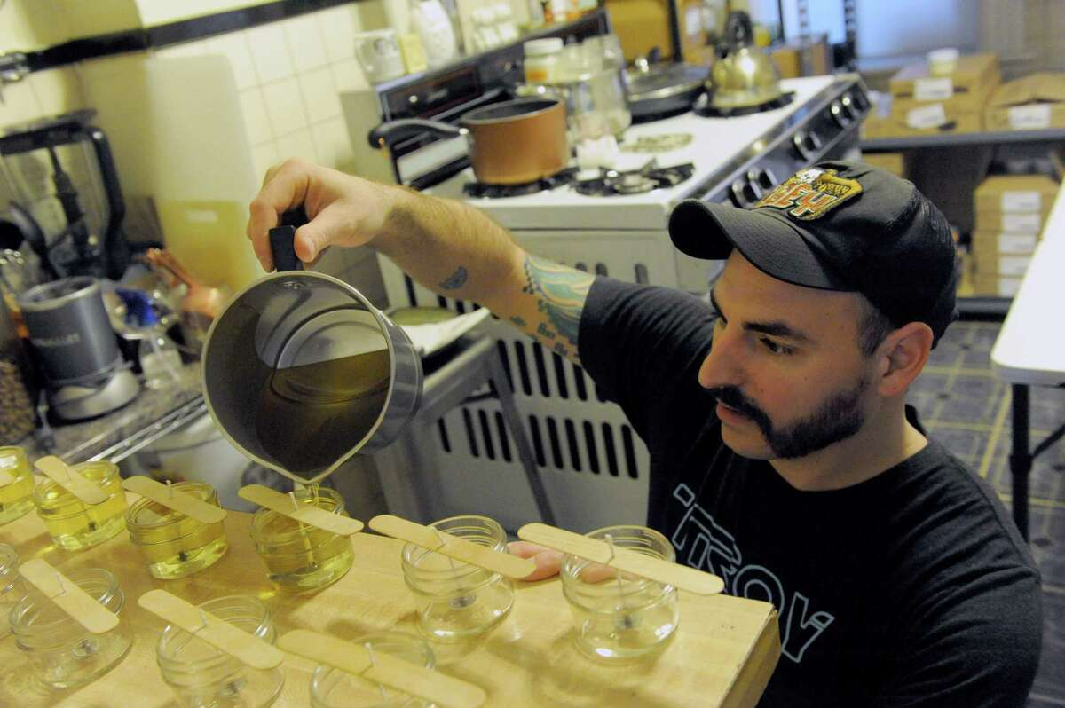 Mike Capritta makes candles on Thursday, March 10, 2016, in Troy, N.Y. Capritta and his wife started selling these candles online and in the Honest Weight Co-Op about a year ago. He makes the candles in the kitchen of his house, which was built in 1890. (Michael P. Farrell/Times Union)