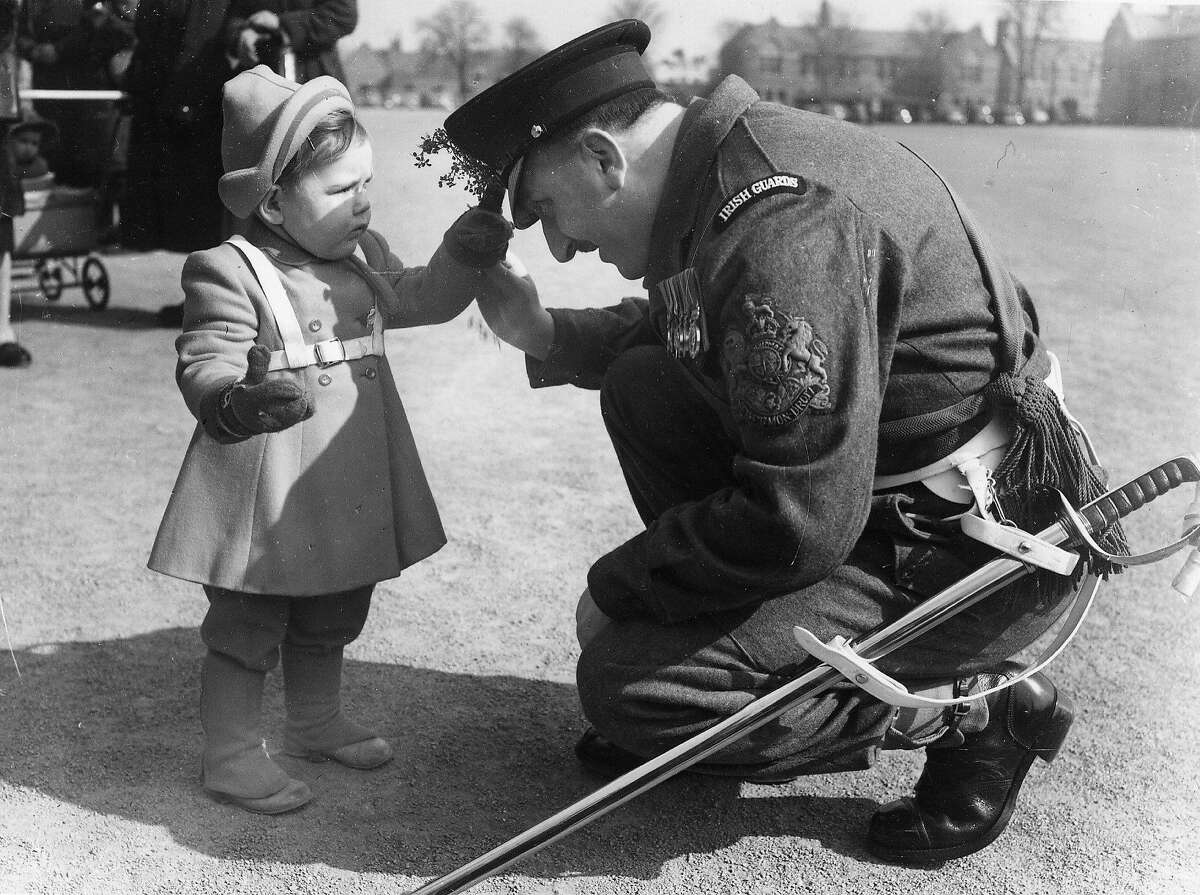 Susan Hendry, aged 2, puts a sprig of shamrock in the cap of RSM J Slater during the St Patrick's Day Parade, commanded by her father, Major Hendry, at the Irish Guards Depot, Caterham, Surrey, England.