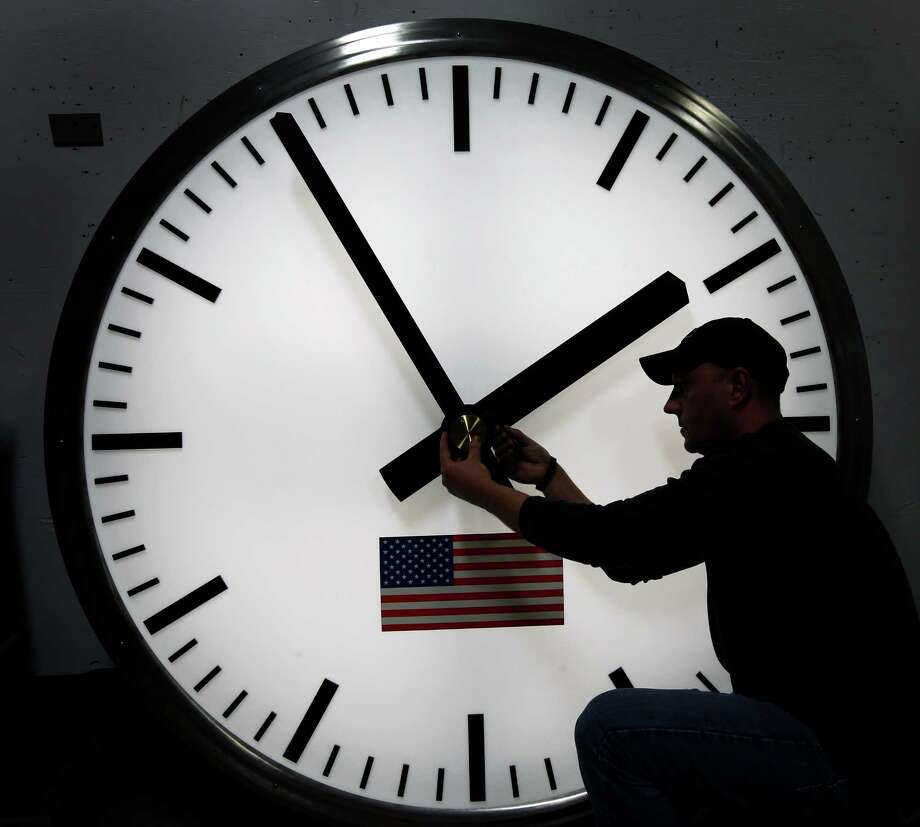 Dave LeMote uses an allen wrench to adjust hands on a stainless steel tower clock at Electric Time Company, Inc. in Medfield, Mass., Friday, March 7, 2014. Most Americans will set their clocks 60 minutes forward before heading to bed Saturday night, but daylight saving time officially starts Sunday at 2 a.m. local time (0700GMT). (AP Photo/Elise Amendola) Photo: Elise Amendola, STF / Associated Press / AP