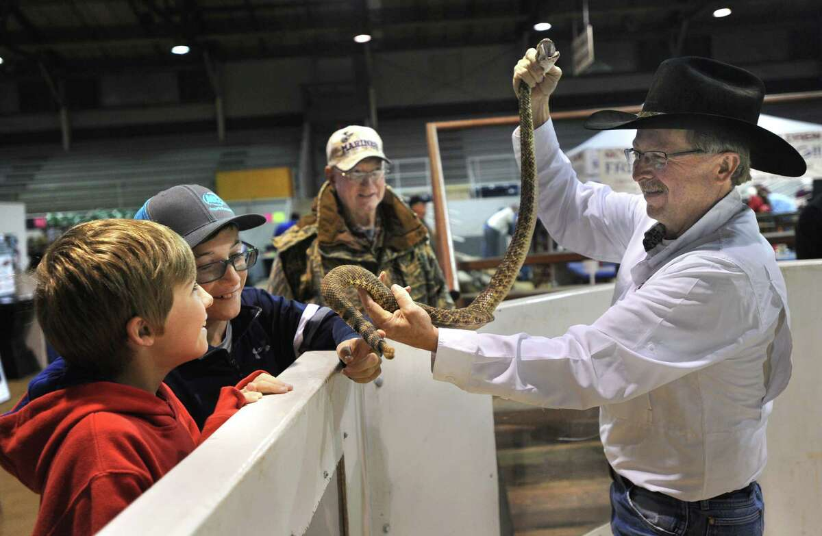 Larry Martin, right, lets visitors touch a live rattlesnake at the annual World's Largest Rattlesnake Round Up Friday, March 11, 2016, in Sweetwater, Texas.