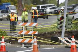 A traffic light protrudes from a sinkhole at the intersection of Rheem Boulevard and Center Street as PG&E crews look over the site on Monday, March 14, 2016 in Moraga, California.