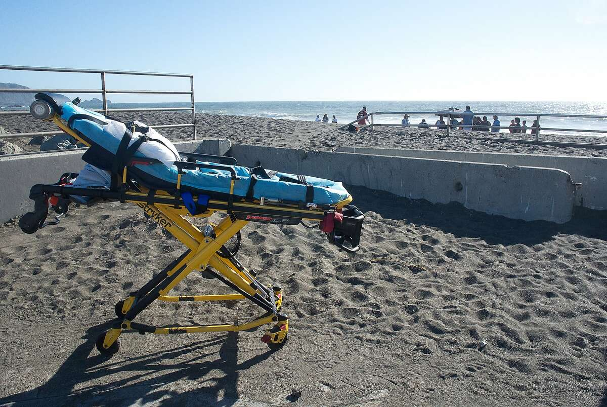 In this June 2014 photo, emergency medical responders (background) attempt to revive a stricken swimmer who may have suffered a heart attack. Note the height of the sand at the beach entrance.