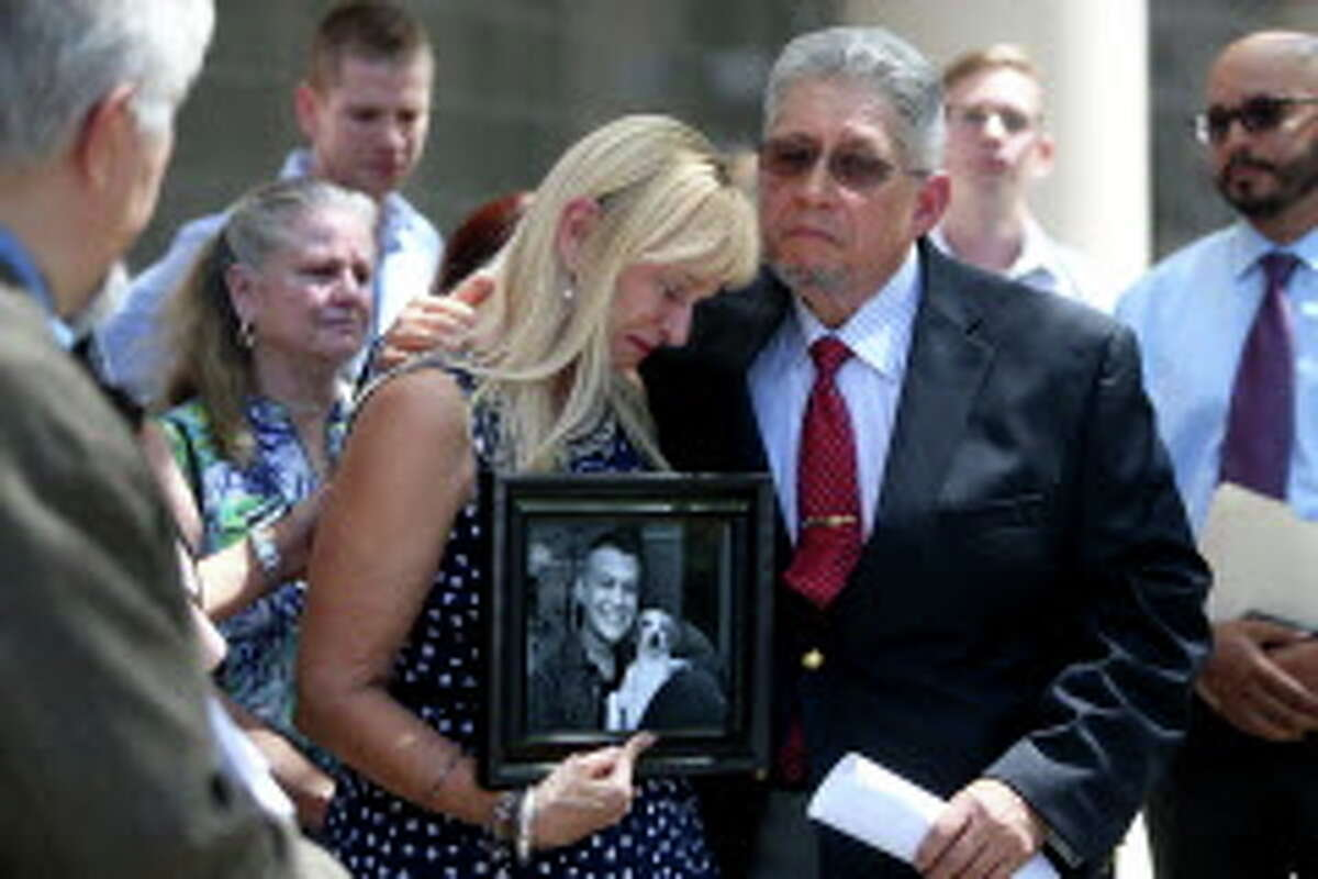 """Diane Jacobs, holding a photo of her son Jesse Jacobs, is comforted by her husband, also named Jesse Jacobs, after announcing they have filed a federal lawsuit against Galveston County at the United States District Court Southern District Monday, March 14, 2016, in Houston, Texas. The Galveston County Medical Examiner determined Jesse's cause of death to be """"abrupt discontinuation of long term alprazolam medication."""" Jesse died one year ago today. He went to jail to serve out a short sentence."""